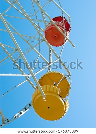 Two opened colored booths ferris wheel against a cloudless blue sky - stock photo