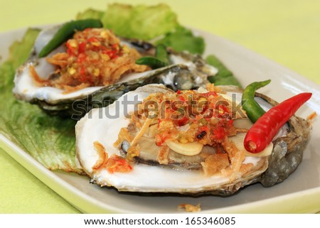 Two opened oysters with Thai spicy garlic and chili on the plate /selective focus - stock photo