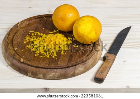 Two orange and zest on wooden cutting board. From the series Ingredients for desserts. - stock photo