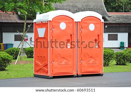 Two Orange Color Portable Toilet In The Park - stock photo