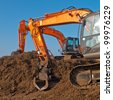 Two orange excavators during sunset on a building site - stock photo