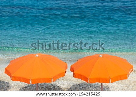 Two orange parasol on the beach. - stock photo