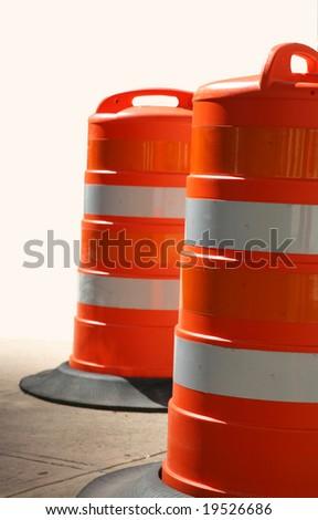 Two Orange Traffic Barrels on Concrete - stock photo