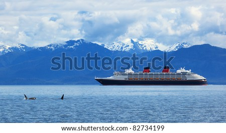 Two orca whales     and cruise  liner are shown on snow mountains   background, Alaska, the USA - stock photo