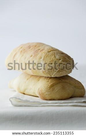 Two organic ciabatta bread over white cloth  - stock photo