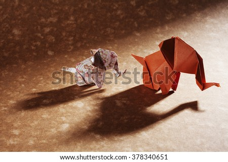 Two origami elephants, floral and orange, isolated on craft paper background. - stock photo