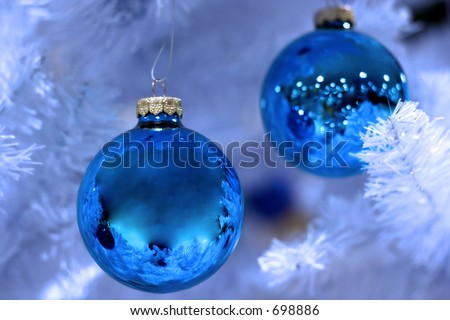 two ornaments on frosted christmas tree - stock photo