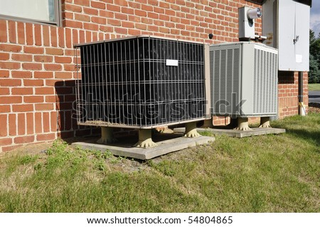 Two outdoor air conditioning units for a small office building. - stock photo