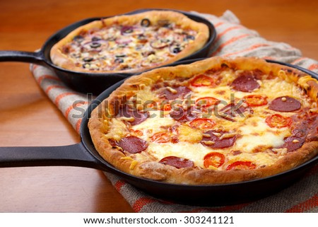 Two oven cooked cast iron skillet pan pizzas on wooden table - stock photo