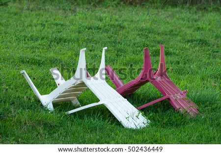 Two overturned chairs on a lawn