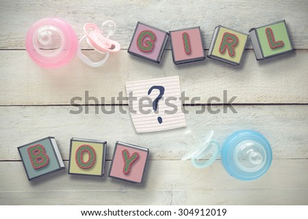 Two pacifiers and baby bottles, pink and blue. Next, some cube letters composing the words GIRL and BOY. A question mark symbolizing uncertainty and doubt. All the objects are on a white wooden table. - stock photo