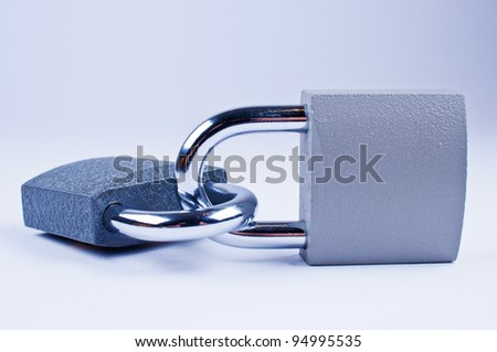 Two padlocks with a key on grey background - stock photo