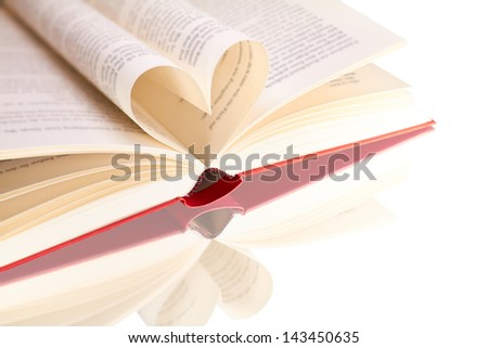 Two pages of a book are curved into a heart shape. - stock photo