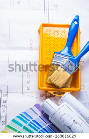 two paint brushes in tray on blueprints  - stock photo