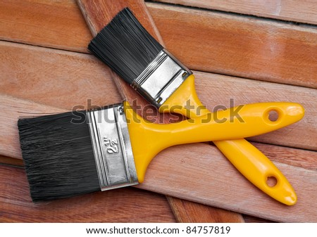Two paint brushes on wooden boards - stock photo