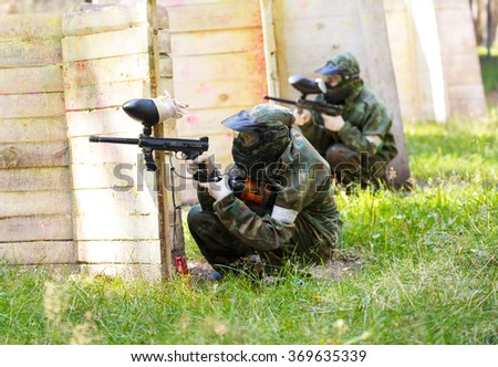 Two paintball players behind wooden fortifications - stock photo