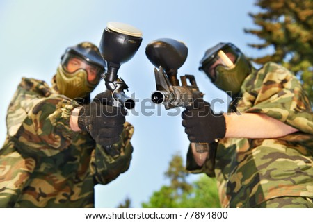 two paintball players in protective clothing aiming guns outdoors - stock photo