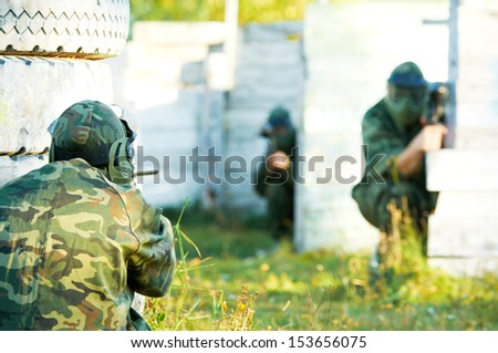 Two paintball sport players in prootective uniform and mask aiming and shoting with gun outdoors - stock photo