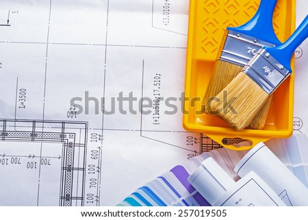 two paintbrushes in paint can with rolled blueprints on color sampler with copyspace - stock photo