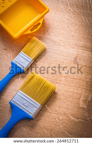 two paintbrushes with blue handles and yellow paint can on wooden board construction concept  - stock photo