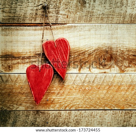 Two painted red hearts hanging on the wooden weathered rustic background - stock photo