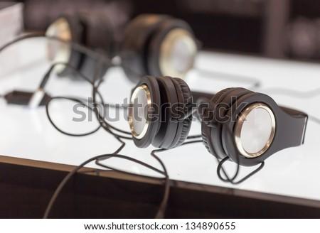 Two pair black headphones on table - stock photo