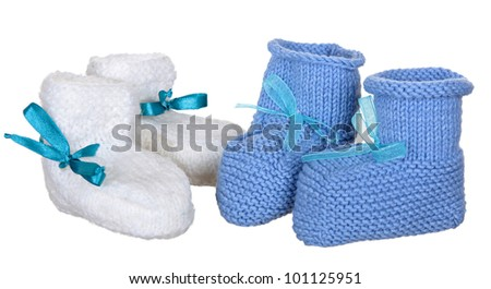 two pair of blue and white knit children's bootees on a white background - stock photo