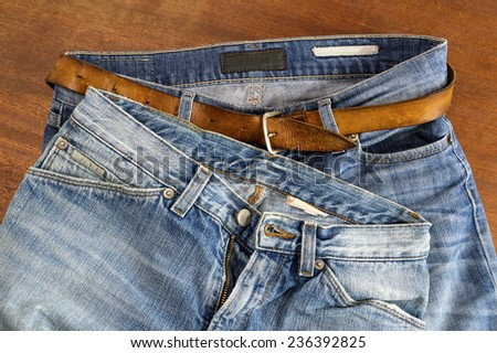 Two pair of blue jeans on a wood surface - stock photo