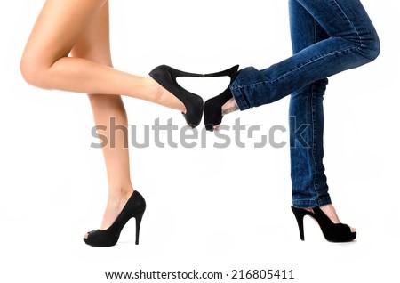 Two pair of female legs in studio - stock photo