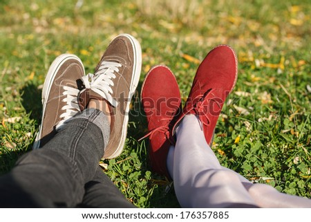 two pair of male and female legs in shoes lying on green grass - stock photo