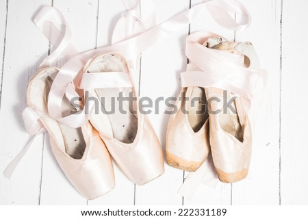 Two pair of satin russian pink ballet pointes new and old with long ribbons lying on a white wooden background. Shabby chic style