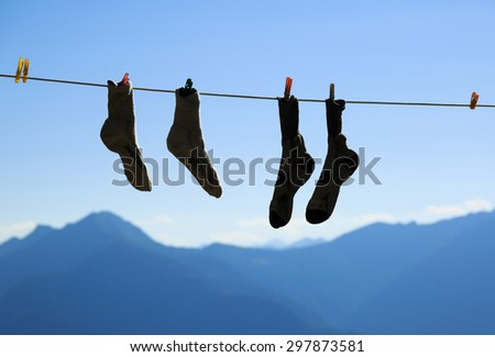 Two pair of socks drying on a clothes line during an adventurous hike in the mountains. - stock photo