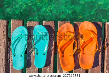 two pair of turquoise green and orange  flip-flops on the wooden planks of a jetty  over the sea