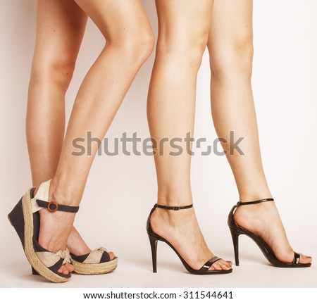 two pair of woman legs in hight heels shoes isolated on white - stock photo