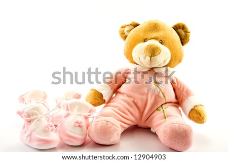 Two pairs of baby's slippers and teddy bear - stock photo
