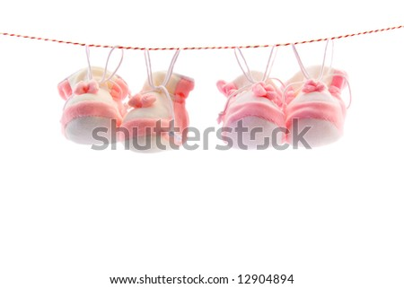 Two pairs of baby's slippers hanging on a rope. Including copy space. - stock photo