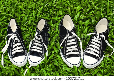 Two pairs of black canvas shoes, sneakers, chucks over green grass background - stock photo