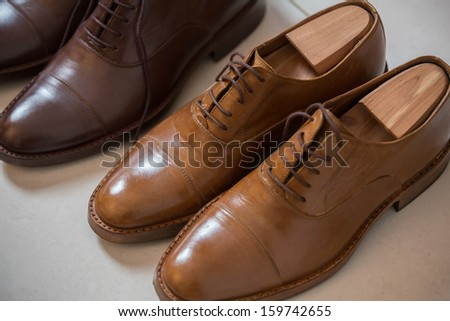 Two pairs of brown handmade classic men's shoes  with a shoe pads and stretchers inside and beside the shoes - stock photo