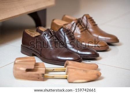 Two pairs of brown handmade classic men's shoes  with a shoe pads and stretchers inside and beside the shoes