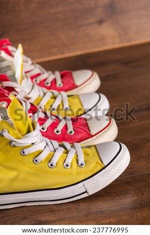 two pairs of cool youth red and yellow  gym shoes white laces   on brown wooden floor  standing in line side view    - stock photo