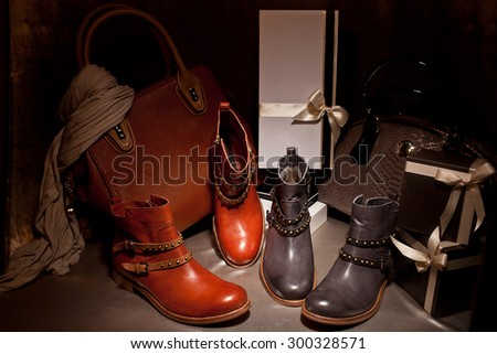 Two pairs of elegant female boots with a leather bag on a golden background autumn present - stock photo
