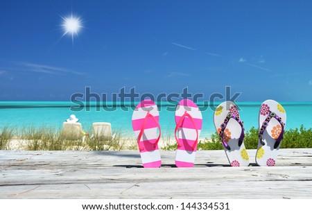 Two pairs of flip-flops against Atlantic. Exuma, Bahamas - stock photo
