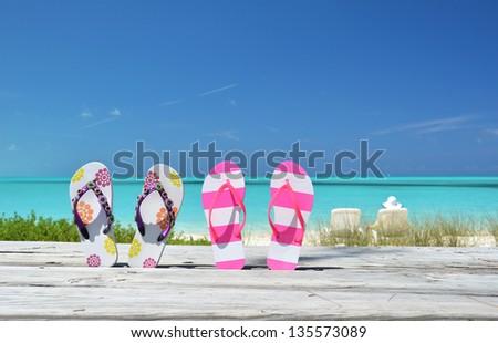Two pairs of flip-flops against ocean. Exuma, Bahamas - stock photo