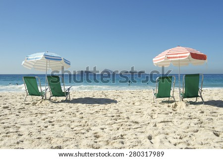 Two pairs of green beach chairs sit empty umbrellas on a quiet morning on Ipanema Beach Rio de Janeiro Brazil