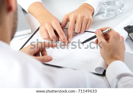 Two pairs of hands passing over business plan - stock photo