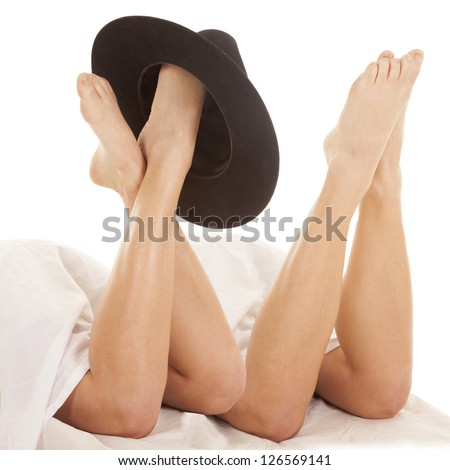 Two pairs of legs coming out from under the sheet with a hat on one foot. - stock photo