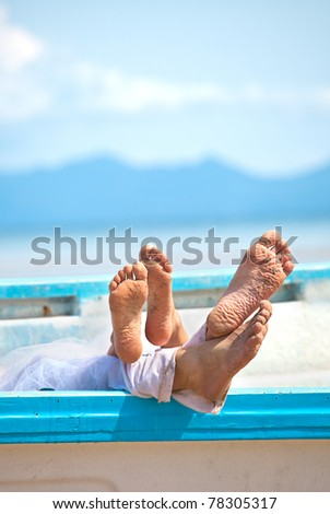 two pairs of legs in the boat on the beach - stock photo