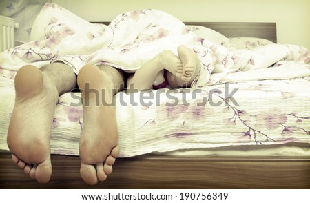 Two pairs of legs of the happy family in bed - father and child - stock photo