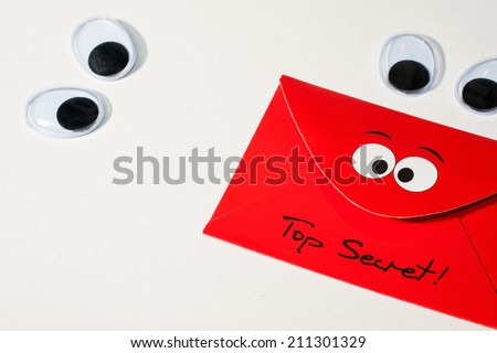 "Two pairs of movable plastic eyes on a white background look on a red envelope with the words ""Top Secret"" - stock photo"