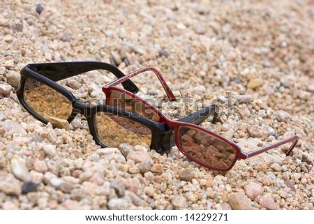 two pairs of sunglasses on the beach - stock photo